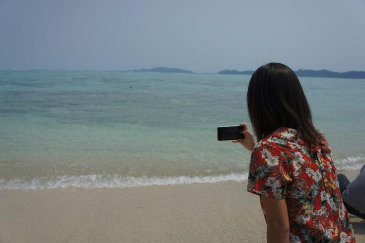 石垣島のビーチで写真を撮る女性